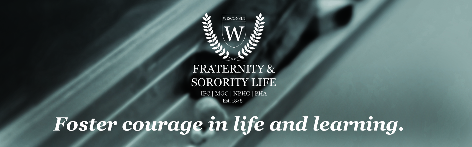 "Black and white photo of eraser and chalk on chalkboard tray with the Fraternity & Sorority Life logo at the top and ""foster courage in life and learning"" at the bottom."