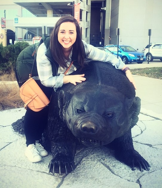 Photo of Maggie Hayes with a Badger statue in front of Camp Randall.